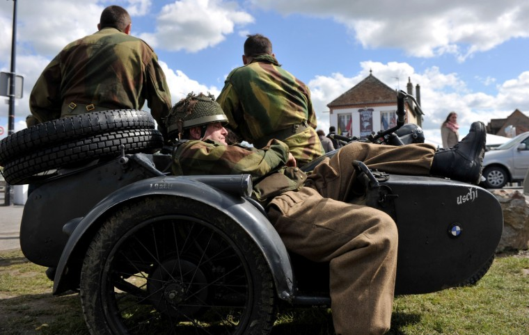 "World War II enthusiasts and reenactors dressed as WWII British soldiers sit on a vintage BMW military motorcycle and sidecar on June 4, 2014 in front of the cafe ""Gondree"", the first house liberated by Allied troops on the night of June 5 to 6, 1944, in Benouville, western France, two days before the start of the D-Day commemorations. (Guillaume Souvant/Getty Images)"