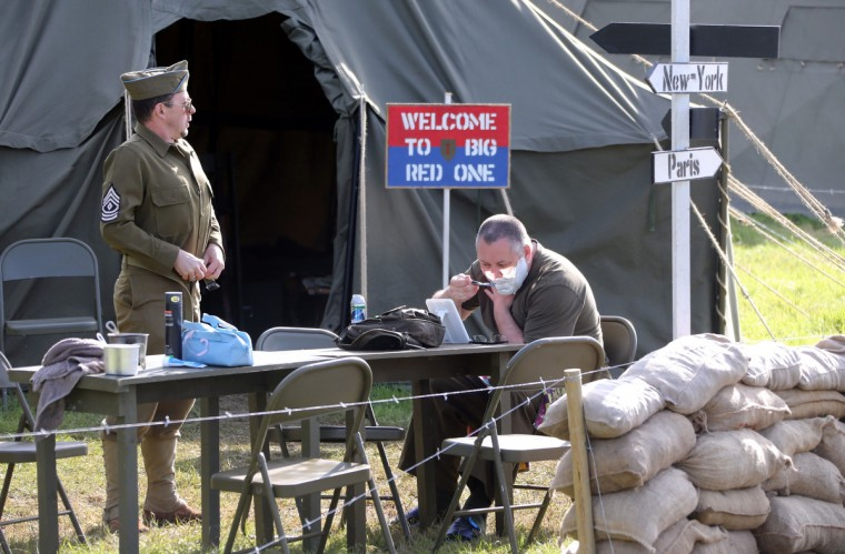 Men dressed in vintage US military uniforms shave in the morning, in Colleville Montgomery, western France, on June 5, 2014, one day before the start of the D-Day commemorations. (Ludovic Marin/Getty Images)