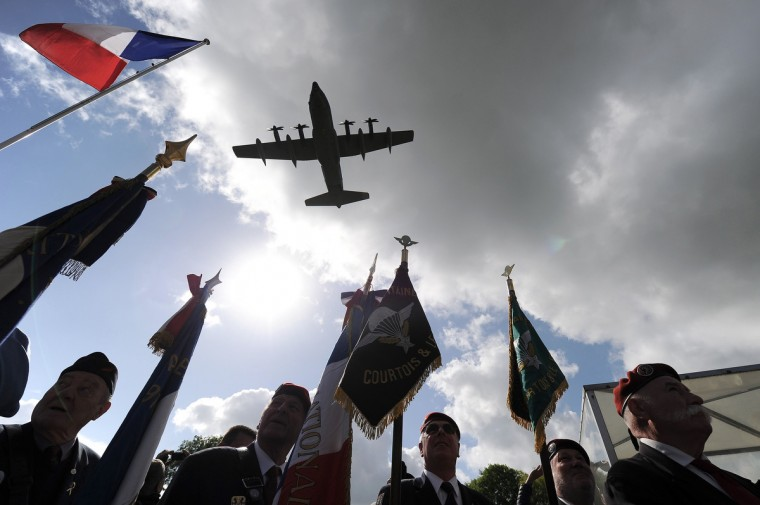 A US military plane flies over a US-German D-Day commemoration ceremony in honor of airborne soldiers on June 5, 2014 in Picauville, northern France. (Jean-Sebastien Evrard/Getty Images)