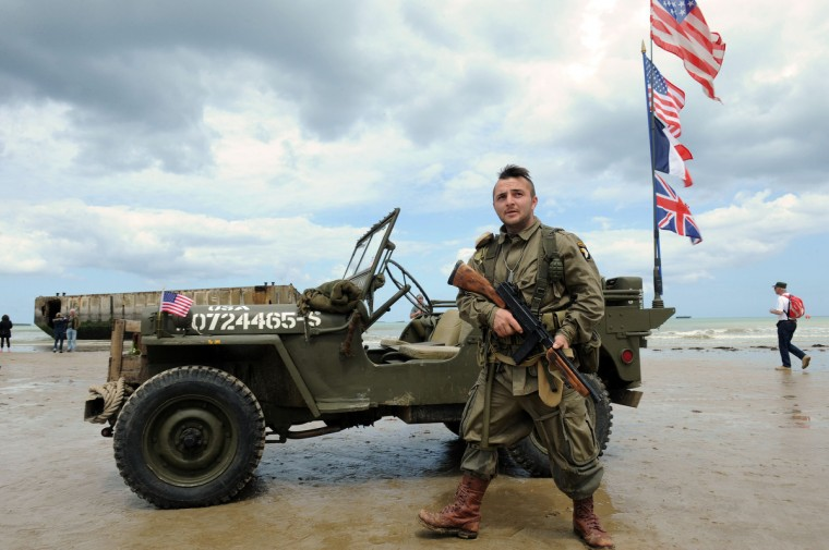 A French man dressed in vintage military clothing holds a gun next to an old American military jeep on the beachside in Arromanches-les-Bains, northern France, on June 5, 2014, one day before the start of the D-Day commemorations. (Jean-Francois Monier/Getty Images)
