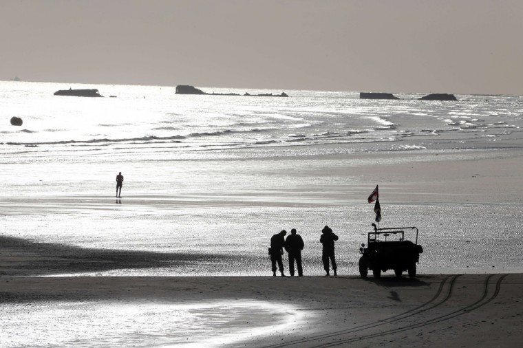 Men dressed in vintage World War II US military uniforms stand next to a Willis jeep, on the beach, in the morning in Arromanches, western France, on June 5, 2014, a day before the start of the D-Day commemorations. (Ludovic Marin/Getty Images)
