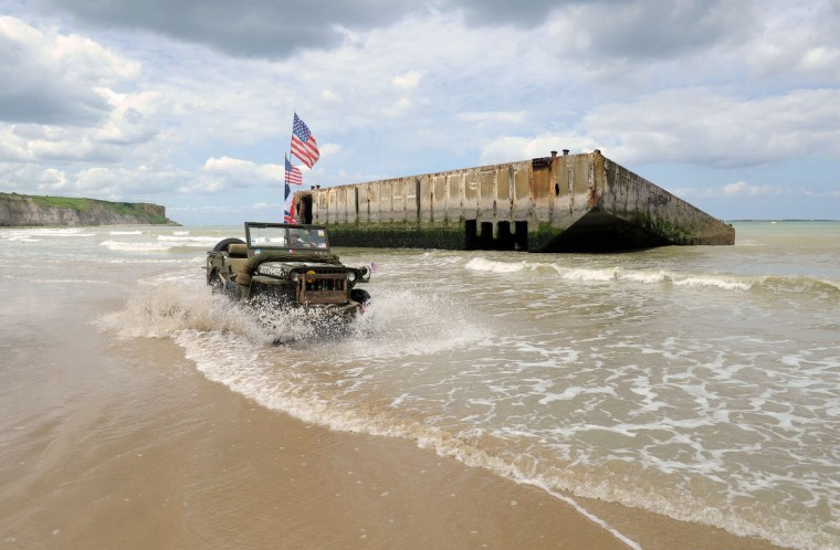 A French man dressed in vintage military clothing drives an old American military jeep on the beachside in Arromanches-les-Bains, northern France, on June 5, 2014, one day before the start of the D-Day commemorations. (Jean-Francois Monier/Getty Images)