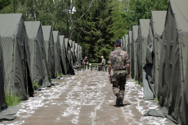 "A French soldier walks in the ""Koenig Camp"" military camp, in Breteville-sur-Odon, northwestern France, on June 5, 2014, where all forces mobilized for D-Day commemorations are gathered. (Charly Triballeau/Getty Images)"