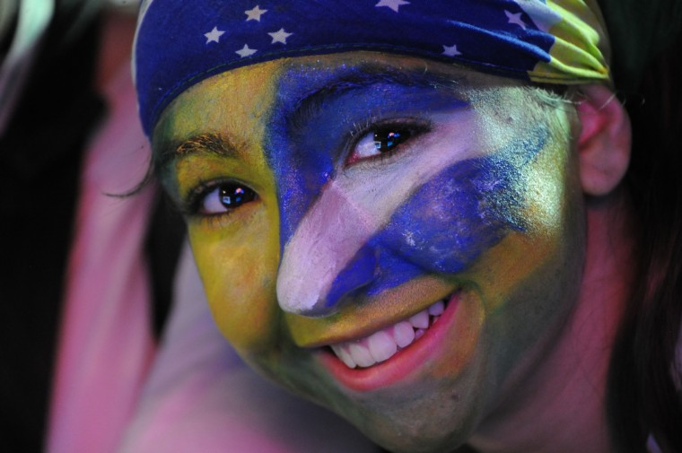 A Brazilian supporter smiles at the Fan Fest in Rio de Janeiro on June 12, 2014. Brazil was nervously gearing up for the start of the World Cup on Thursday with the host nation preparing to launch the month-long carnival as scattered protests broke out just hours from kick-off. (Tasso Marcelo/Getty Images)