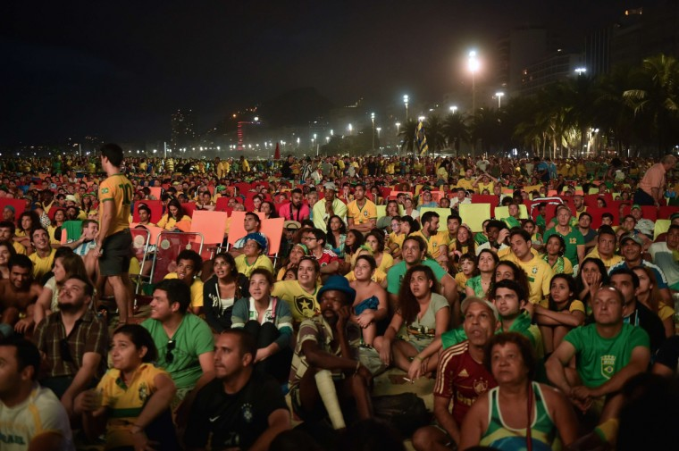 People watch on a huge screen the Brazil vs Croatia opening match during the FIFA Fan Fest in Copacabana Beach in Rio de Janeiro, Brazil on June 12, 2014. Brazil's ambivalence toward the World Cup was on full display as the country geared up for the game, the sea of green and yellow in some areas contrasting with the billowing smoke from burning garbage and clouds of tear gas that filled the air as military police and protesters clashed in the nation's financial hub. (Yasuyoshi Chiba/Getty Images)