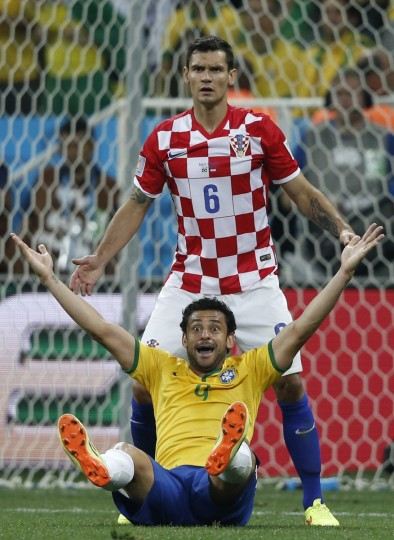 Brazil's forward Fred (front) is fouled by Croatia's defender Dejan Lovren to be awarded a penalty during a Group A football match between Brazil and Croatia at the Corinthians Arena in Sao Paulo during the 2014 FIFA World Cup on June 12, 2014. (Adrian Dennis/Getty Images)