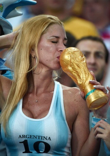 An Argentina fan kisses a fake trophy before for the Group F football match between Argentina and Bosnia-Hercegovina at the Maracana Stadium in Rio De Janeiro during the 2014 FIFA World Cup on June 15, 2014. (Damien Meyer/Getty Images)
