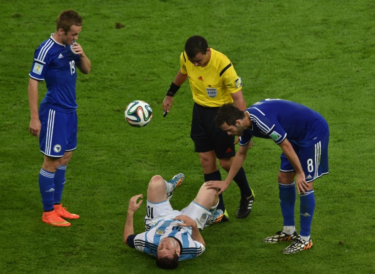 Salvadoran referee Joel Aguilar (C) checks on Argentina's forward and captain Lionel Messi (C, ground) along with Bosnia-Hercegovina's midfielder Miralem Pjanic and forward Edin Visca (L) after he fell during the Group F football match between Argentina and Bosnia Hercegovina at the Maracana Stadium in Rio De Janeiro during the 2014 FIFA World Cup on June 15, 2014. (Yasuyoshi Chiba/Getty Images)