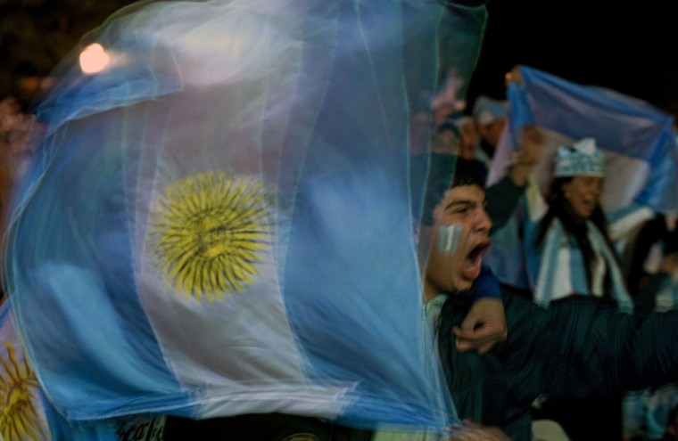Argentinian football fans celebrate a goal as they watch the FIFA World Cup match against Bosnia-Hercegovina on a giant screen at San Martin Square, in Buenos Aires, on June 15, 2014. (Alejandro Pagni/Getty Images)