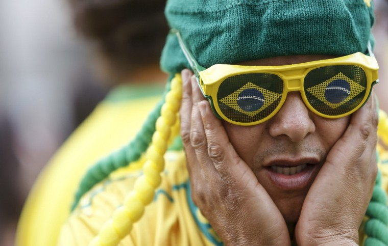 A Brazilian supporter gestures before the start of the 2014 FIFA World Cup Brazil vs Mexico match at the FIFA Fan Fest public viewing event in Sao Paulo, Brazil on June 17, 2014. (Miguel Schincariol/Getty Images)