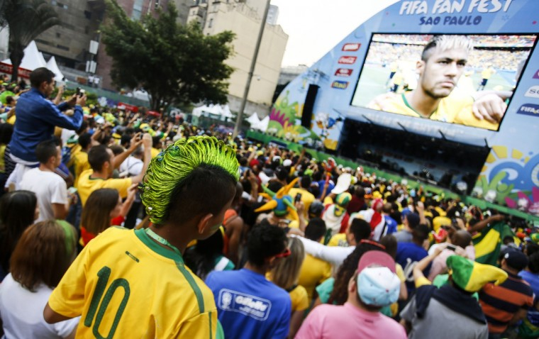 Brazilian supporters take snapshots before the start of the 2014 FIFA World Cup Brazil vs Mexico match at the FIFA Fan Fest public viewing event in Sao Paulo, Brazil on June 17, 2014. (Miguel Schincariol/Getty Images)