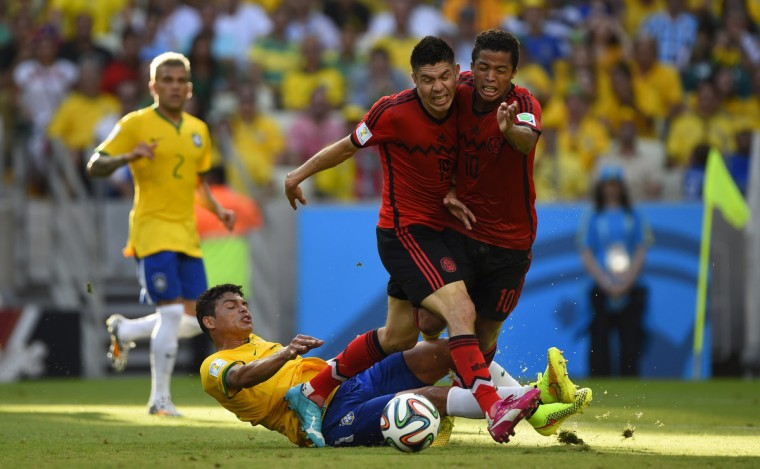 Brazil's defender Thiago Silva (down) vies with Mexico's forward Giovani Dos Santos (R) and Mexico's forward Oribe Peralta (C) during a Group A football match between Brazil and Mexico in the Castelao Stadium in Fortaleza during the 2014 FIFA World Cup on June 17, 2014. (Odd Andersen/Getty Images)