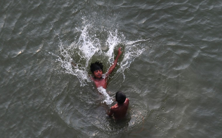 Indian boys cool off with a swim in the Yamuna river on a hot summer day in Allahabad. Sultry weather conditions gripped north India as most parts of the region experienced another hot and humid day with the mercury maintaining its up trend. (Sanjay Kanojia/Getty Images)