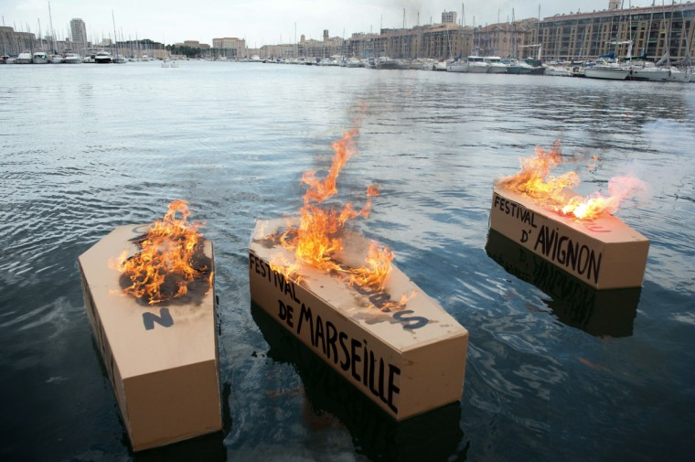 "Three coffin-shaped carton boxes set on fire reading ""Avignon Festival"" (R) and ""Marseille Festival"" (C) floating on the water in Marseille, southern France. Protestors took part in a demonstration on June 18 called by French artists and entertainment workers, known in France as ""intermittents du spectacle"", to protest against the French government's plan to reform their status. (Bertrand Langlois/Getty Images)"