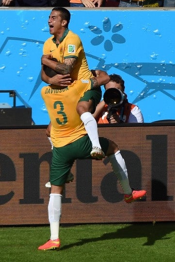Australia's forward Tim Cahill celebrates with a teammate after scoring during a Group B football match between Australia and the Netherlands at the Beira-Rio Stadium in Porto Alegre during the 2014 FIFA World Cup on June 18, 2014. (Luis Acosta/AFP/Getty Images)