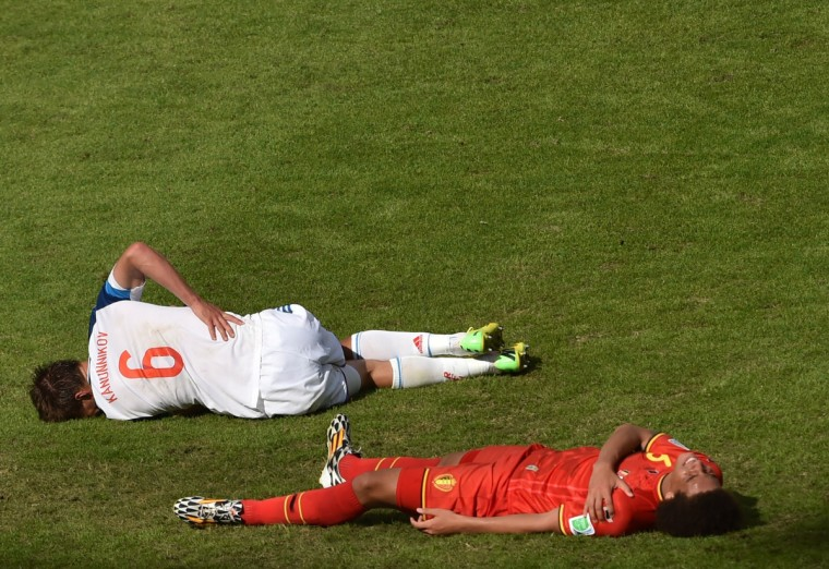 Russia's forward Maksim Kanunnikov (L) and Belgium's midfielder Axel Witsel lie on the ground following a tackle during a Group H football match between Belgium and Russia at the Maracana Stadium in Rio de Janeiro during the 2014 FIFA World Cup on June 22, 2014. (Yasuyoshi Chiba/Getty Images)