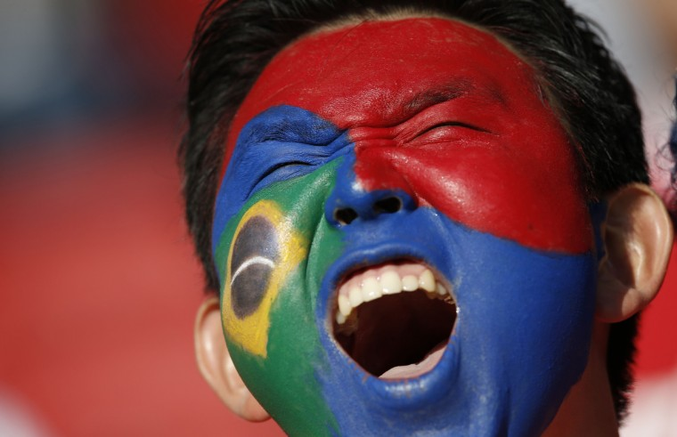 A South Korea fan with his face painted in the colors of his country and of Brazil cheers prior to a Group H football match between South Korea and Algeria at the Beira-Rio Stadium in Porto Alegre during the 2014 FIFA World Cup on June 22, 2014. (Adrian Dennis/Getty Images)