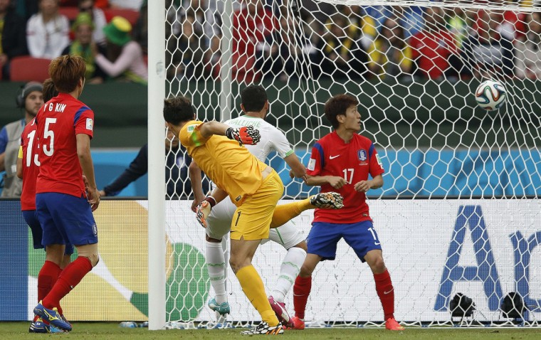 Algeria's defender Rafik Halliche (C) scores in the nets of South Korea's goalkeeper Jung Sung-Ryong during a Group H football match between South Korea and Algeria at the Beira-Rio Stadium in Porto Alegre during the 2014 FIFA World Cup on June 22, 2014. (Adrian Dennis/Getty Images)