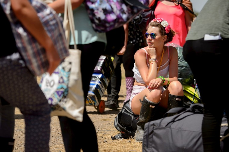A festival goer sits on her back pack as the gates open at the Glastonbury Festival of Music and Performing Arts in Somerset, south west England, on June 25, 2014. (Leon Neal/Getty Images)