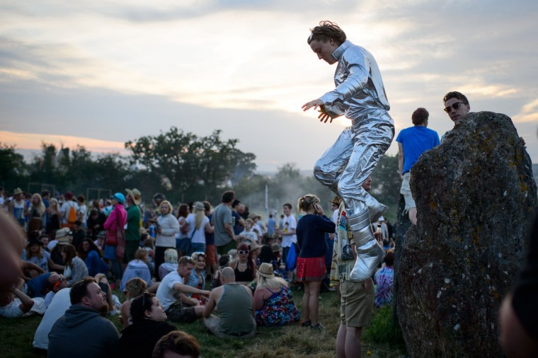 A man in a spacesuit jumps from one of the standing stones in the stone circle, as revelers gather ahead of this weekends Glastonbury Festival of Music and Performing Arts on Worthy Farm in Somerset, south west England, on June 25, 2014. (Leon Neal/Getty Images)