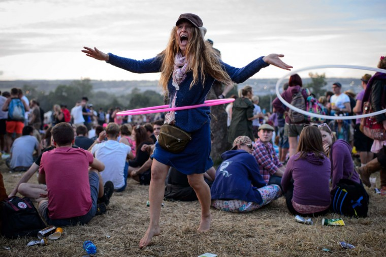 A festival goer uses a hula hoop, as revelers gather ahead of this weekends Glastonbury Festival of Music and Performing Arts on Worthy Farm in Somerset, south west England, on June 25, 2014. (Leon Neal/Getty Images)