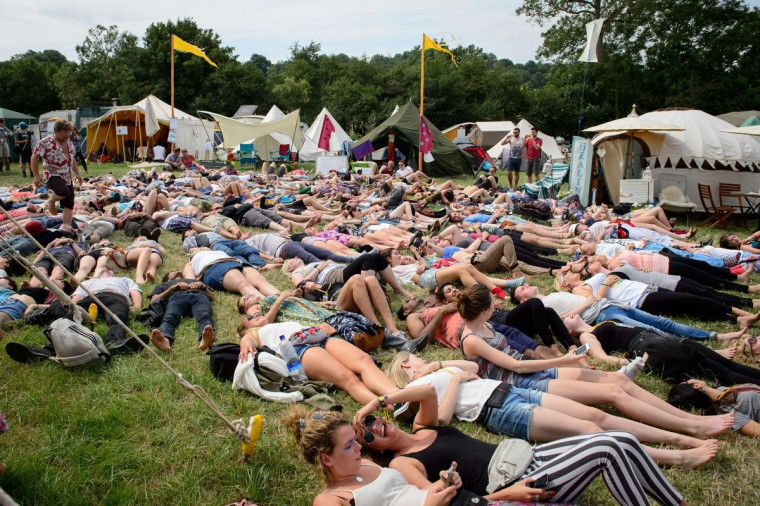 "Festival goers take part in a ""Yoga Laughter"" session in the Green Fields, as revellers gather ahead of this weekends Glastonbury Festival of Music and Performing Arts on Worthy Farm near Pilton in Somerset, south west England, on June 26, 2014. (Leon Neal/Getty Images)"