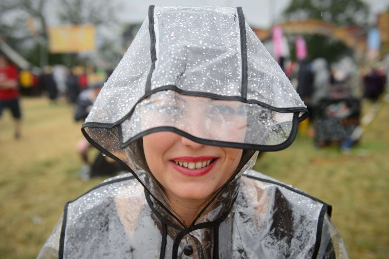 A girl wears a waterproof coat during the first rain showers, as revellers gather ahead of the Glastonbury Festival of Music and Performing Arts in Somerset, southwest England, on June 26, 2014. (Leon Neal/Getty Images)