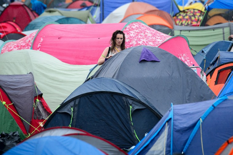 A girl stands among the tents during the first rain showers, as revellers gather ahead of the Glastonbury Festival of Music and Performing Arts in Somerset, southwest England, on June 26, 2014. (Leon Neal/Getty Images)