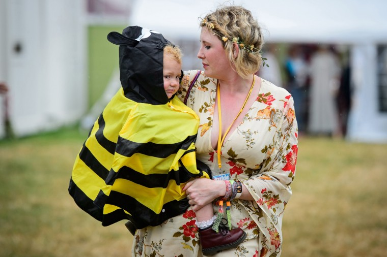 A child in a bee design waterproof poncho is carried through the backstage area, as revellers gather ahead of the Glastonbury Festival of Music and Performing Arts in Somerset, southwest England. (Leon Neal/Getty Images)