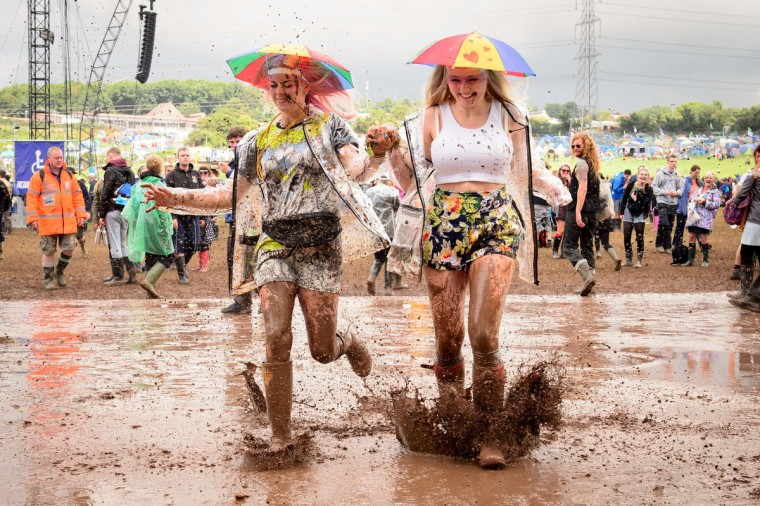 Revellers run through a puddle as they pose for photographers, on the first official day of the Glastonbury Festival of Music and Performing Arts on Worthy Farm in Somerset, south west England, on June 27, 2014. (Leon Neal/Getty Images)