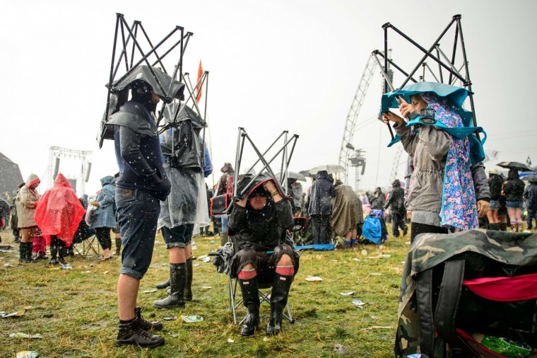 Festivalgoers face up to the heavy rain, on the first official day of the Glastonbury Festival of Music and Performing Arts in Somerset, southwest England, on June 27, 2014. (Leon Neal/Getty Images)