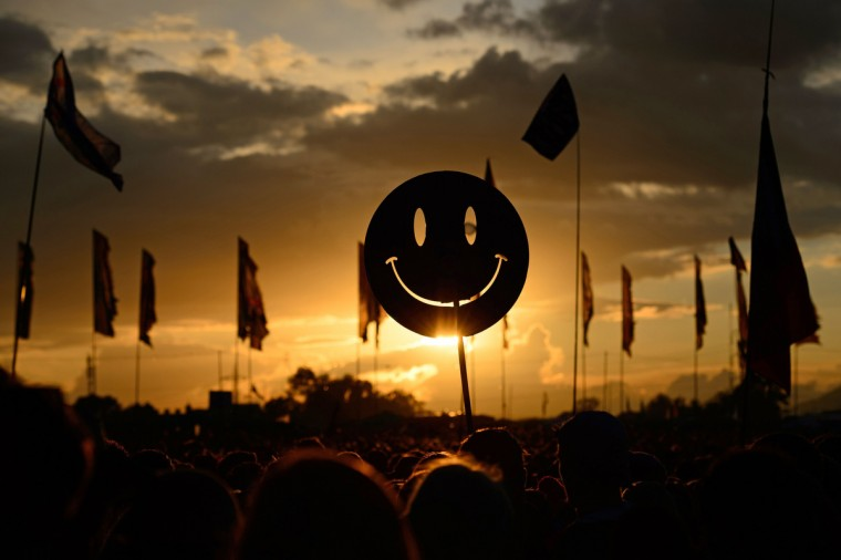 A smiley face sign is carried through the crowds as the sun sets on the first official day of the Glastonbury Festival of Music and Performing Arts in Somerset, southwest England, on June 27, 2014.(Leon Neal/Getty Images)