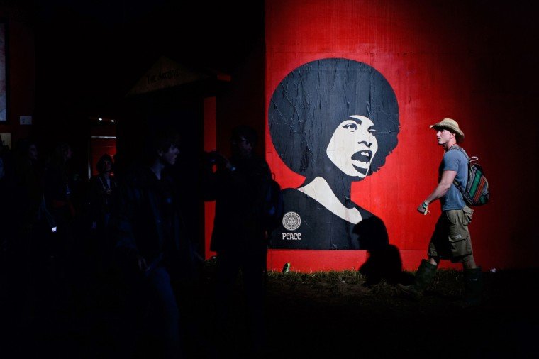 "A man walks past a wall mural in the ""Shangri-La"" area, on the second day of the Glastonbury Festival of Music and Performing Arts in Somerset, southwest England, on June 28, 2014. (Leon Neal/Getty Images)"