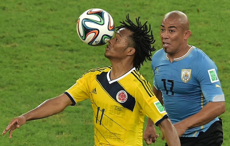 Colombia's midfielder Juan Guillermo Cuadrado (L) and Uruguay's midfielder Egidio Arevalo Rios vie during the Round of 16 football match between Colombia and Uruguay at the Maracana Stadium in Rio de Janeiro during the 2014 FIFA World Cup in Brazil on June 28, 2014. (Gabriel Bouys/Getty Images)
