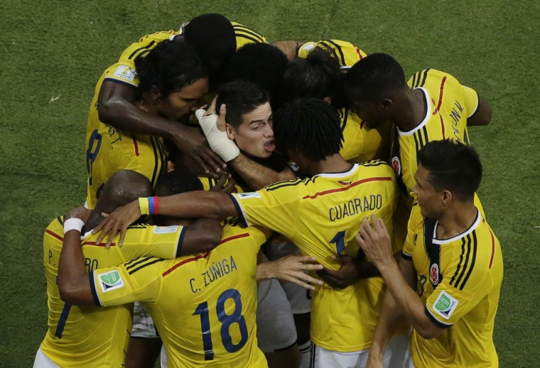 Colombia's midfielder James Rodriguez (C) is mobbed by teammates as he celebrates scoring a goal during the Round of 16 football match between Colombia and Uruguay at The Maracana Stadium in Rio de Janeiro on June 28, 2014,during the 2014 FIFA World Cup. (Dana Felipe/Getty Images)