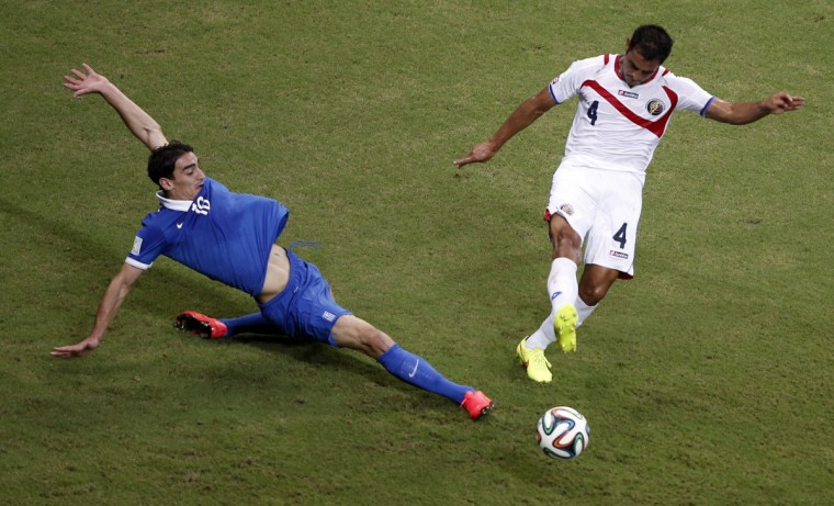 Costa Rica's defender Michael Umana (R) challenges Greece's midfielder Lazaros Christodoulopoulos during the round of 16 football match between Costa Rica and Greece at Pernambuco Arena in Recife during the 2014 FIFA World Cup on June 29, 2014. (Adrian Dennis/Getty Images)