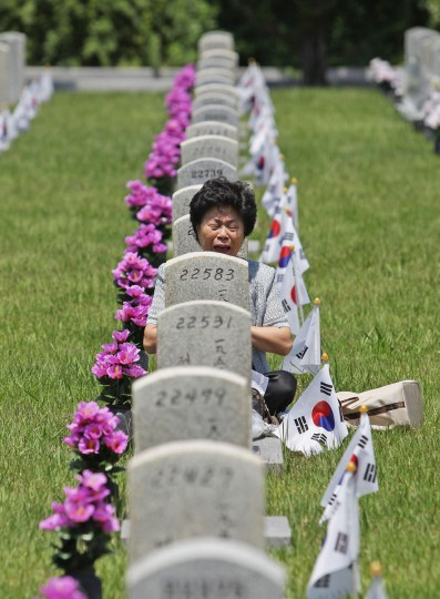 A woman visits the grave of her relative who died during the Korean War at Seoul National Cemetery on June 6, 2014 in Seoul, South Korea. South Korea marks the 59th anniversary of the Memorial Day for people who died during the military service in the 1950-53 Korean War. (Chung Sung-Jun/Getty Images)