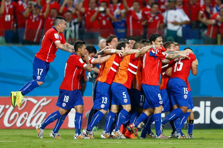 Jean Beausejour of Chile (Right) celebrates scoring his teams third goal with teammates during the 2014 FIFA World Cup Brazil Group B match between Chile and Australia at Arena Pantanal on June 13, 2014 in Cuiaba, Brazil. (Phil Walter/Getty Images)