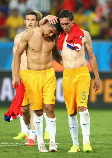 Tim Cahill (Left) and Mark Milligan of Australia embrace after being defeated by Chile 3-1 during the 2014 FIFA World Cup Brazil Group B match between Chile and Australia at Arena Pantanal on June 13, 2014 in Cuiaba, Brazil. (Cameron Spencer/Getty Images)
