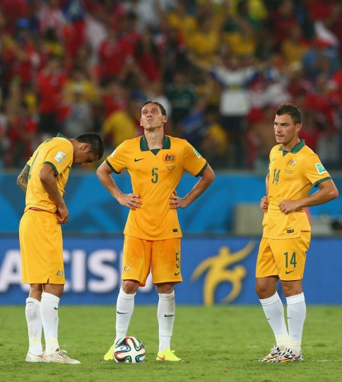Tim Cahill, from left, Mark Milligan and James Troisi of Australia wait to kickoff after allowing a third goal to Chile during the 2014 FIFA World Cup Brazil Group B match between Chile and Australia at Arena Pantanal on June 13, 2014 in Cuiaba, Brazil. (Cameron Spencer/Getty Images)