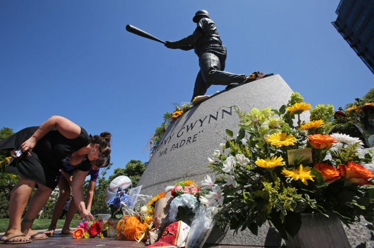 Fans place flowers at the base of a statue of the late San Diego Padres great Tony Gwynn at Petco Park, where the Padres play, June 16, 2014 in San Diego, California. Gwynn died this morning after a lengthy battle with cancer, according to published reports. He was 54. (Getty Images/Bill Wechter)