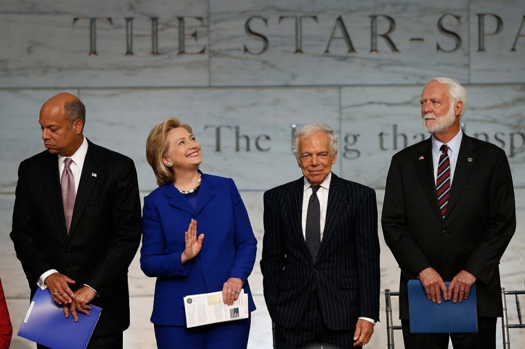 Former U.S. Secretary of State Hillary Clinton (2nd L) waves to spectators during a naturalization ceremony with Ralph Lauren (2nd R), U.S. Secretary of Homeland Security Jeh Johnson (L), and Smithsonian Secretary Wayne Clough (L) at the National Museum of American History June 17, 2014 in Washington, DC. Lauren was presented the James Smithson Bicentennial Medal during a citizenship ceremony welcoming 15 new Americans for his contributions to the preservation of the Star-Spangled Banner. (Getty Images/Win McNamee)