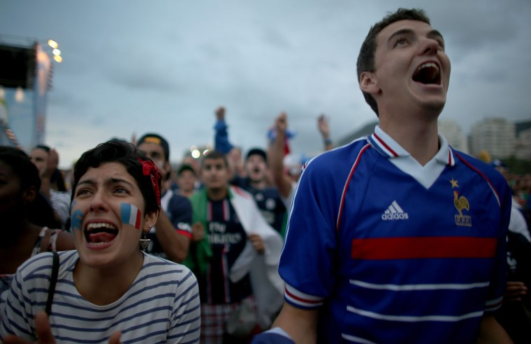 French soccer team fans react to their team scoring against the Switzerland team as they watch on the screen setup at the Word Cup FIFA Fan Fest during on Copacabana beach June 20, 2014 in Rio de Janeiro, Brazil. (Photo by Joe Raedle/Getty Images)