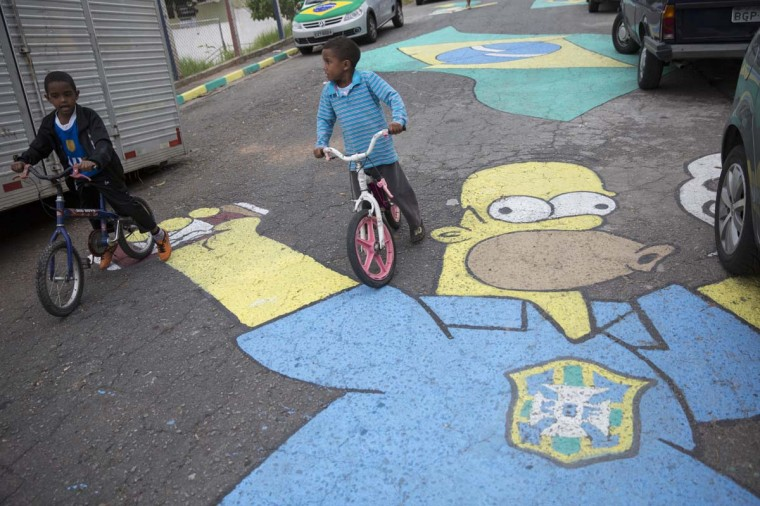 Children ride bikes over a painting of cartoon character Homer Simpson wearing a Brazilian football shirt on a street in the poor neighbourhood of Itaquera, adjacent to the 'Arena de Sao Paulo' stadium, on June 21, 2014 in Sao Paulo, Brazil. The Arena de Sao Paulo, which is reported to have cost in excess of 200 million GBP, hosted the opening match of the 2014 FIFA World Cup and has a capacity of over 61,000. The total cost borne by Brazil for staging the 2014 World Cup is estimated to be 6.5 billion GBP, which critics have argued would have better spent on the millions of Brazilians living in poverty. (Photo by Oli Scarff/Getty Images)