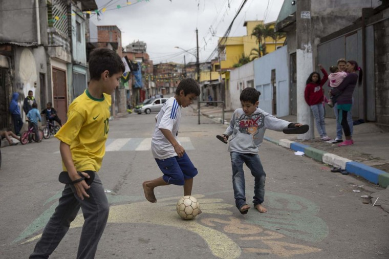 Children play football in the street in the poor neighbourhood of Itaquera, adjacent to the 'Arena de Sao Paulo' stadium, on June 21, 2014 in Sao Paulo, Brazil. The Arena de Sao Paulo, which is reported to have cost in excess of 200 million GBP, hosted the opening match of the 2014 FIFA World Cup and has a capacity of over 61,000. The total cost borne by Brazil for staging the 2014 World Cup is estimated to be 6.5 billion GBP, which critics have argued would have better spent on the millions of Brazilians living in poverty. (Photo by Oli Scarff/Getty Images)