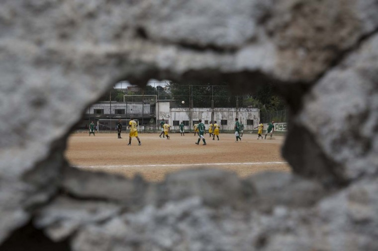 Men play football on the 'Artur Alvim' club's dirt pitch in the poor neighbourhood of Itaquera, adjacent to the 'Arena de Sao Paulo' stadium, on June 21, 2014 in Sao Paulo, Brazil. The Arena de Sao Paulo, which is reported to have cost in excess of 200 million GBP, hosted the opening match of the 2014 FIFA World Cup and has a capacity of over 61,000. The total cost borne by Brazil for staging the 2014 World Cup is estimated to be 6.5 billion GBP, which critics have argued would have better spent on the millions of Brazilians living in poverty. (Photo by Oli Scarff/Getty Images)