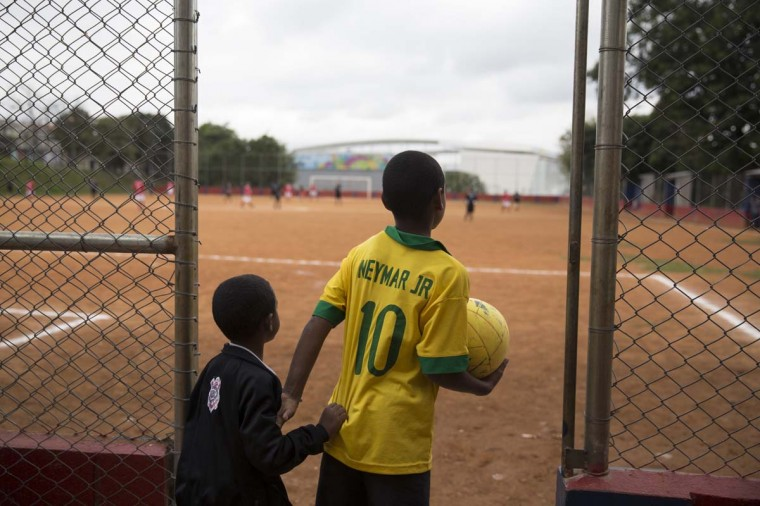Children watch men play football on the 'Artur Alvim' club's dirt pitch in the poor neighbourhood of Itaquera, adjacent to the 'Arena de Sao Paulo' stadium, on June 21, 2014 in Sao Paulo, Brazil. The Arena de Sao Paulo, which is reported to have cost in excess of 200 million GBP, hosted the opening match of the 2014 FIFA World Cup and has a capacity of over 61,000. The total cost borne by Brazil for staging the 2014 World Cup is estimated to be 6.5 billion GBP, which critics have argued would have better spent on the millions of Brazilians living in poverty. (Photo by Oli Scarff/Getty Images)