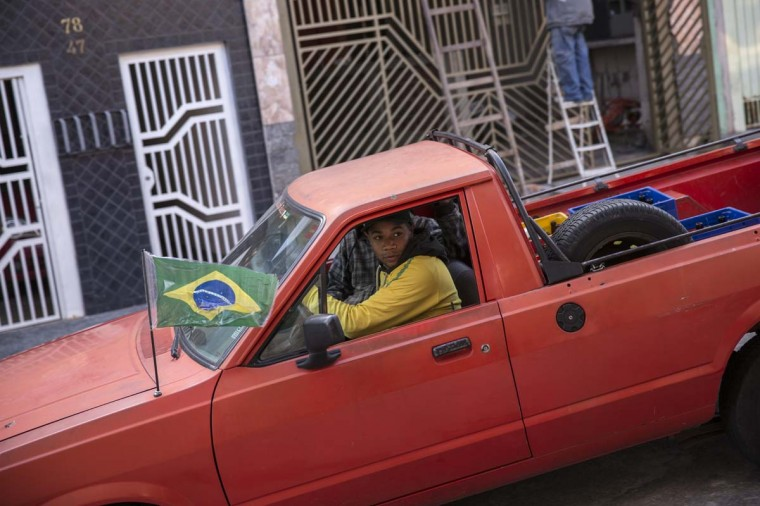 A man wearing a Brazilian football shirt drives a pickup truck through the streets of the poor neighbourhood of Itaquera, adjacent to the 'Arena de Sao Paulo' stadium, on June 21, 2014 in Sao Paulo, Brazil. The Arena de Sao Paulo, which is reported to have cost in excess of 200 million GBP, hosted the opening match of the 2014 FIFA World Cup and has a capacity of over 61,000. The total cost borne by Brazil for staging the 2014 World Cup is estimated to be 6.5 billion GBP, which critics have argued would have better spent on the millions of Brazilians living in poverty. (Photo by Oli Scarff/Getty Images)