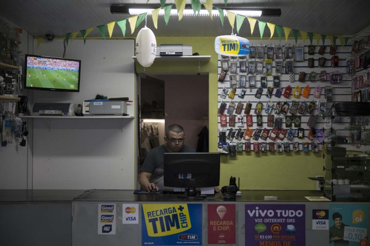 A television shows a World Cup match in phone accessory shop in the poor neighbourhood of Itaquera, adjacent to the 'Arena de Sao Paulo' stadium, on June 21, 2014 in Sao Paulo, Brazil. The Arena de Sao Paulo, which is reported to have cost in excess of 200 million GBP, hosted the opening match of the 2014 FIFA World Cup and has a capacity of over 61,000. The total cost borne by Brazil for staging the 2014 World Cup is estimated to be 6.5 billion GBP, which critics have argued would have better spent on the millions of Brazilians living in poverty. (Photo by Oli Scarff/Getty Images)