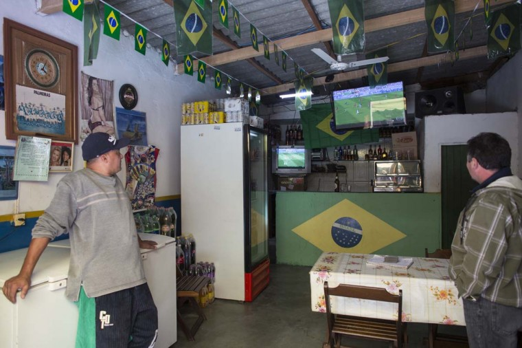 A television shows a World Cup match in a bar in the poor neighbourhood of Itaquera, adjacent to the 'Arena de Sao Paulo' stadium, on June 21, 2014 in Sao Paulo, Brazil. The Arena de Sao Paulo, which is reported to have cost in excess of 200 million GBP, hosted the opening match of the 2014 FIFA World Cup and has a capacity of over 61,000. The total cost borne by Brazil for staging the 2014 World Cup is estimated to be 6.5 billion GBP, which critics have argued would have better spent on the millions of Brazilians living in poverty. (Photo by Oli Scarff/Getty Images)